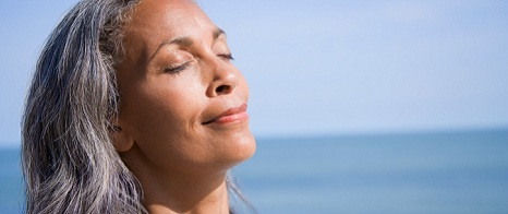 Woman using the warmth of the sun as a relaxation technique