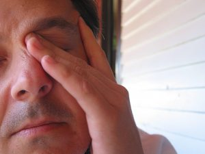 Man with sleep problems rubbing eye